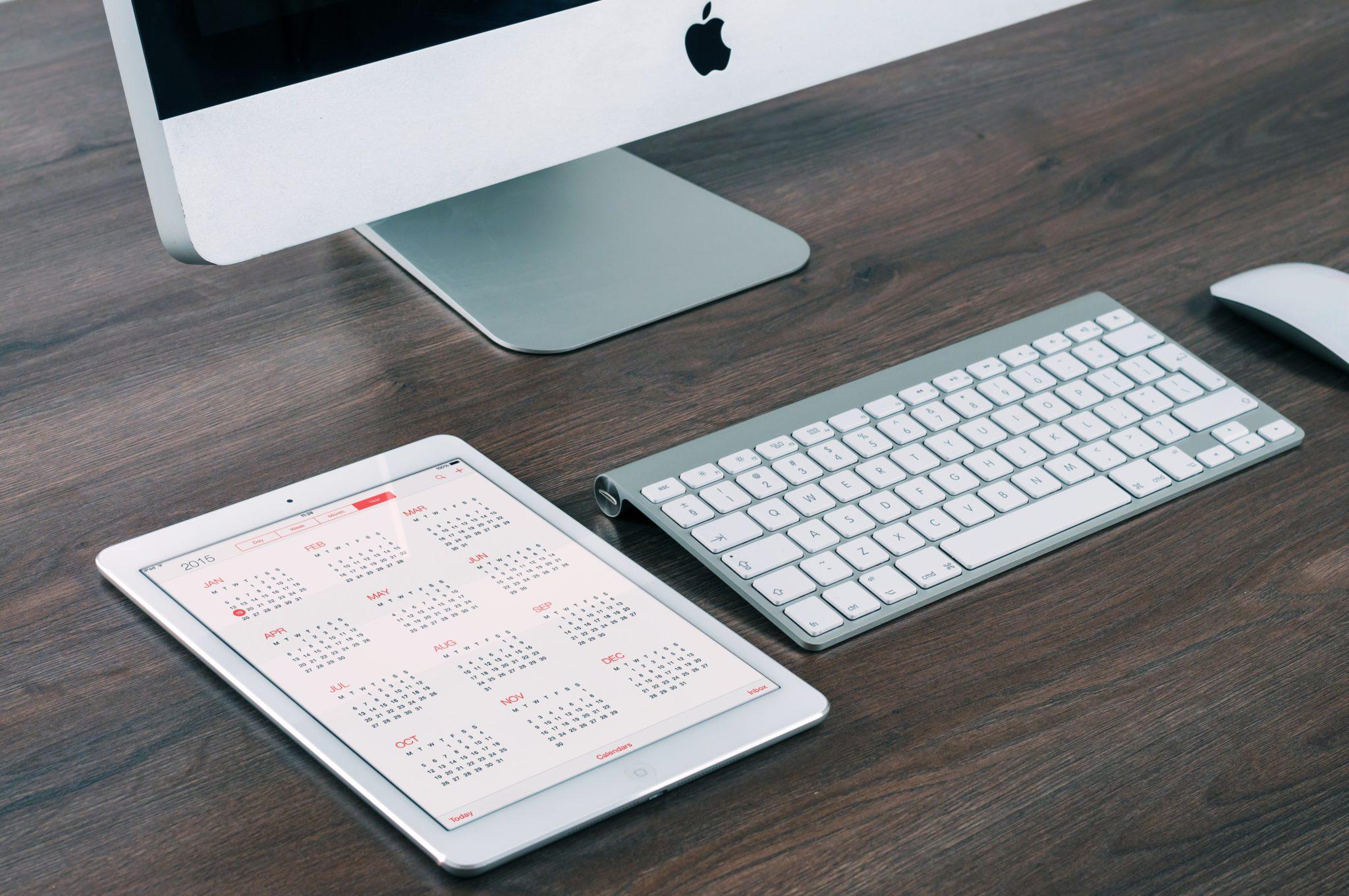 tablet mit kalender neben imac mit tastatur und maus