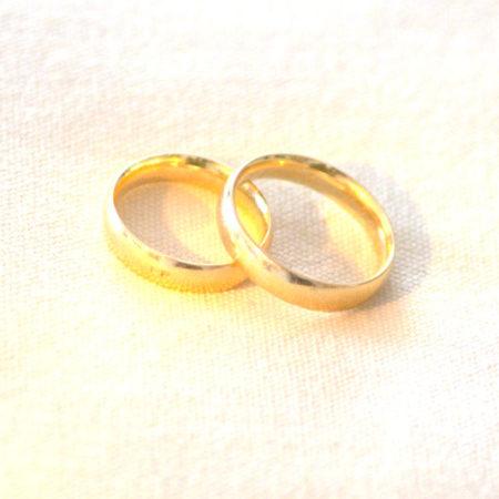 Zwei goldene Ringe auf weissen Kissen